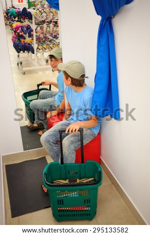 teenager boy sitting on stool in the dressing clothing store and smiling