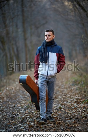 Teenager boy walking on a park alley with his guitar in a case - stock photo