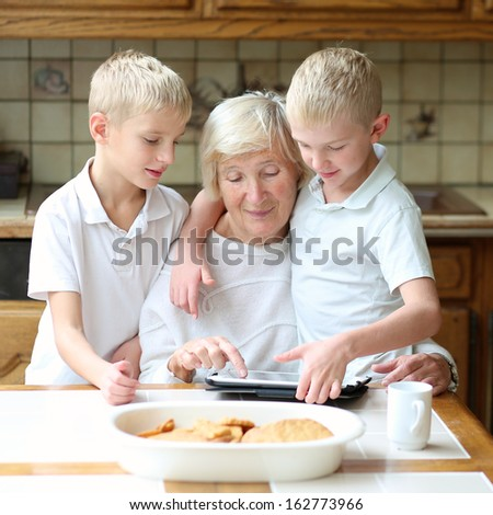 Teenager boys twin brothers enjoying time with grandmother eating cookies, drinking coffee and playing together on tablet computer - stock photo