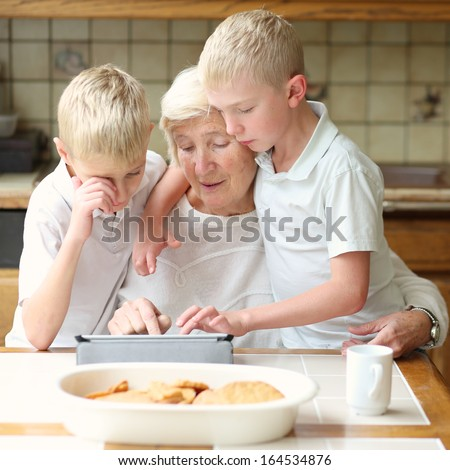 Teenager boys twin brothers teaching grandmother to play on tablet pc, enjoying time together, eating cookies and drinking coffee - stock photo