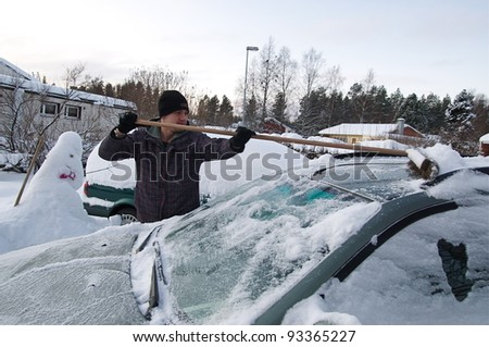 Teenager cleaning car from snow - stock photo