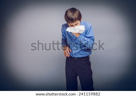 teenager cold flu boy blowing his nose brown hair of European appearance in a handkerchief experiencing discomfort on a gray background cross process - stock photo