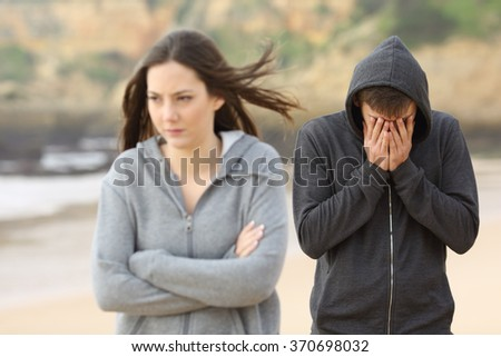 Teenager couple breaking up after argument. The angry girlfriend is rejecting her sad boyfriend - stock photo