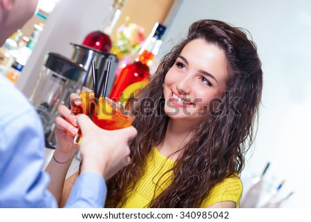 Teenager couple smiling and toasting with bar counter on the background