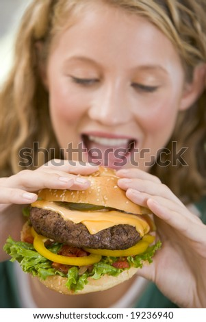 Teenager Eating A Burger - stock photo