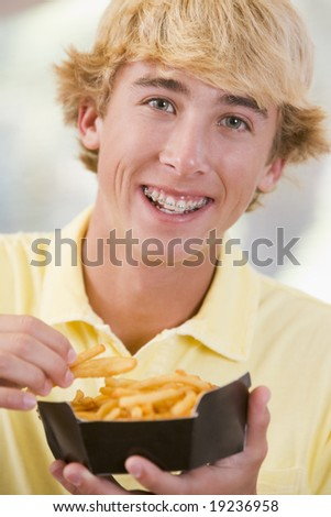 Teenager Eating Fries - stock photo