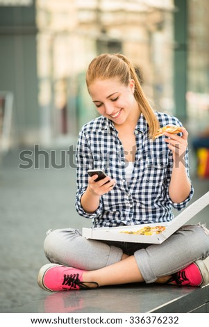 Teenager eating pizza in street and browsing internet on phone - stock photo