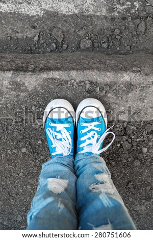 Teenager feet in jeans and blue shoes stand on the street edge. Close-up photo with selective focus and shallow DOF - stock photo