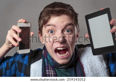 teenager gets crazy with digital media, gray background for fast isolating - stock photo