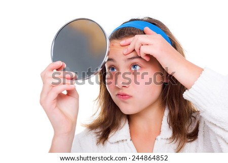 Teenager girl examine her pimples in the mirror - stock photo