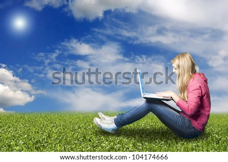 teenager girl in a meadow with her laptop chatting online - stock photo