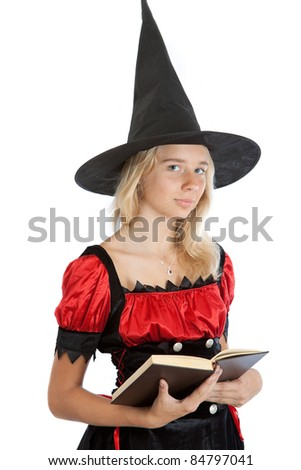 teenager girl in Halloween witch reads magic book - stock photo