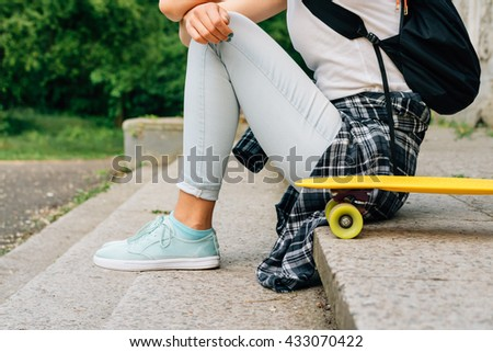 Teenager girl in jeans and a plaid shirt sitting on the steps near her skate outdoors - stock photo