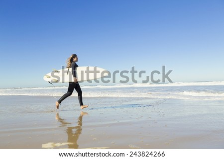 Teenager girl in the beach with her surfboard