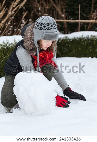Teenager girl making snowman in snowy back yard of her house