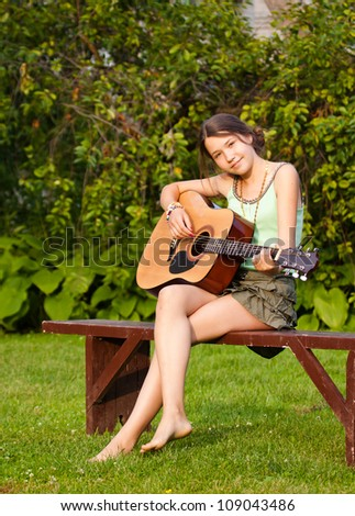 Teenager girl playing the guitar in the park, sitting on the bench - stock photo