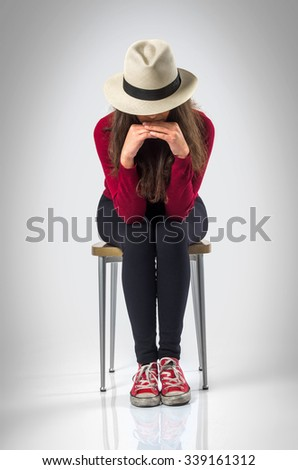 Teenager girl posing in studio wit a chair and a hat over white background - stock photo