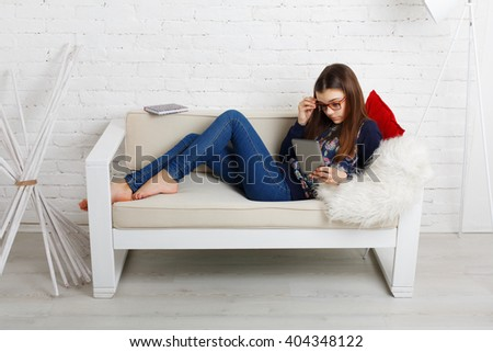 Teenager girl relax home, sitting on sofa with tablet computer. Child wears glasses, eyeglasses. Girl in eyewear with gadget tablet lying on sofa. Adolescence, internet addiction. High key - stock photo