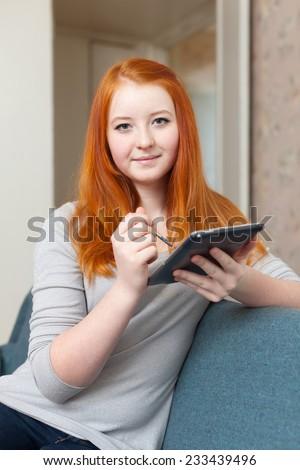 Teenager girl uses electronic book on sofa at home - stock photo