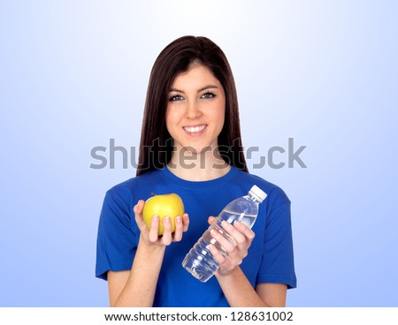 Teenager girl with a yellow apple and water isolated on blue background - stock photo