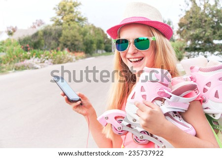 Teenager (girl) with roller skating shoes (inline skates) is using smart phone, listening music with headphone. Happy teen is wearing sunglasses and having fun. Concepts of technology, youth, sport.   - stock photo