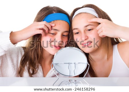 Teenager girls searching for blemishes on theirs skin - stock photo