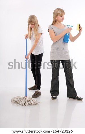 Teenager girls working hard with cleaning utensils - stock photo