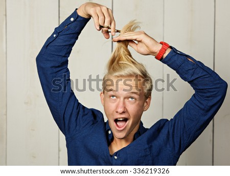 Teenager giving himself a haircut - stock photo