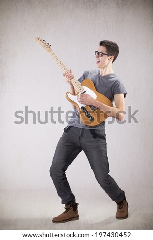 Teenager holding an electric guitar - stock photo