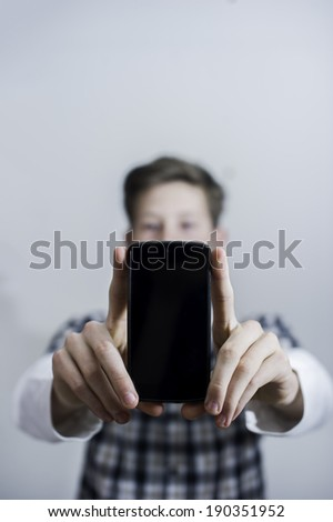 Teenager holding up phone while looking at camera.  - stock photo