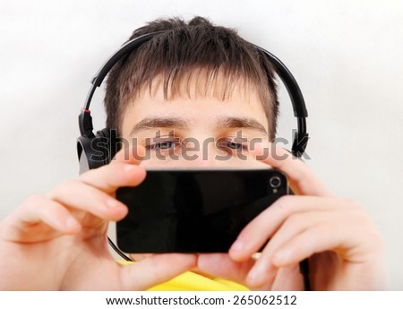 Teenager in Earphones with Cellphone on the White Wall Background closeup - stock photo