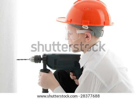 Teenager in protective helmet and spectacles drill the wall