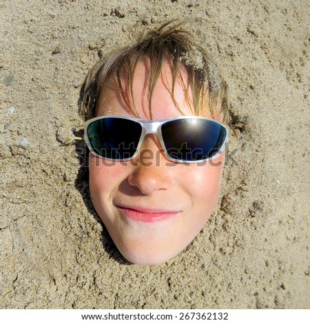 Teenager in Sunglasses in the Sand on the Beach closeup - stock photo