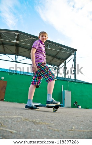 Teenager is getting ready for riding a waveboard - stock photo