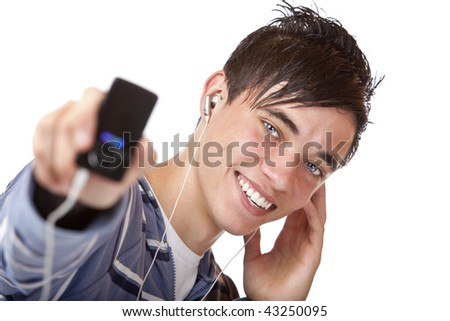 Teenager is listening to music with earphones and holding his mp3 player into camera. Focus on teenager. Isolated on white. - stock photo