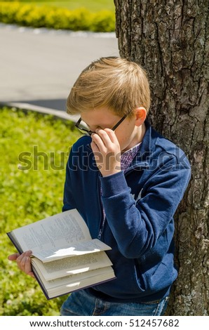 Teenager is reading a book in the park