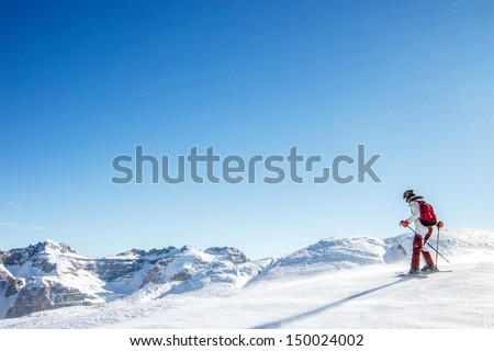 Teenager learning how to ski in the blue sky ant mountains background - stock photo