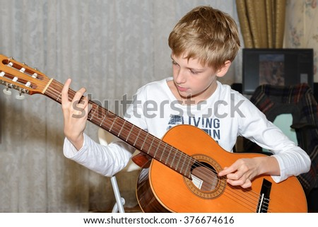 Teenager left-handed playing the classical guitar at his room - stock photo