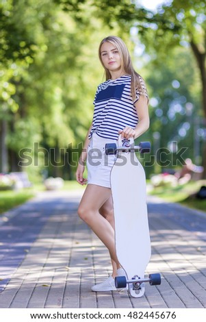 Teenager Lifestyle. Smiling Caucasian Blond Teenager Girl Posing With  Longboard In Park Area Outdise. Vertical Image Orientation