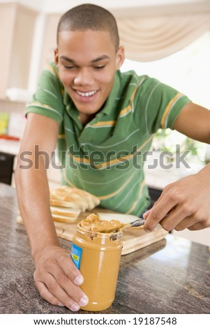 Teenager Making A Peanut Butter Sandwich - stock photo