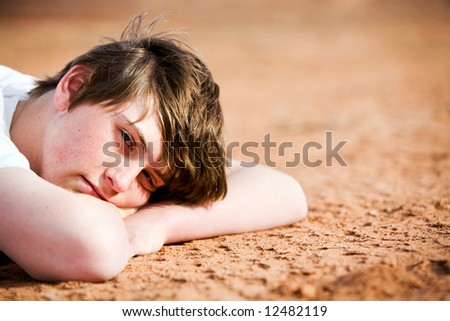teenager male portrait laying on ground - stock photo