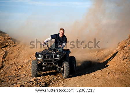 teenager male riding a quad / four wheeler in rural Wyoming - stock photo
