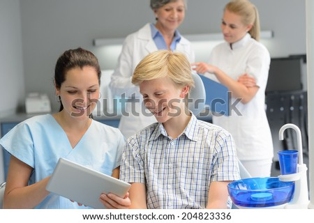Teenager patient with professional dentist team point tablet dental surgery - stock photo