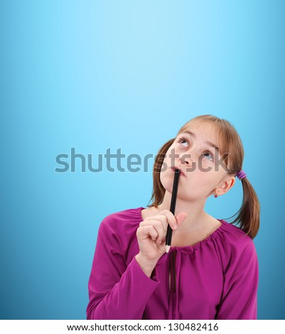 Teenager pigtailed girl thinking and looking left-up to copy space, black pencil in her hand - stock photo