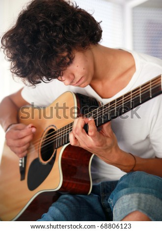 Teenager playing acoustic guitar: Closeup of a young man playing acoustic guitar - stock photo