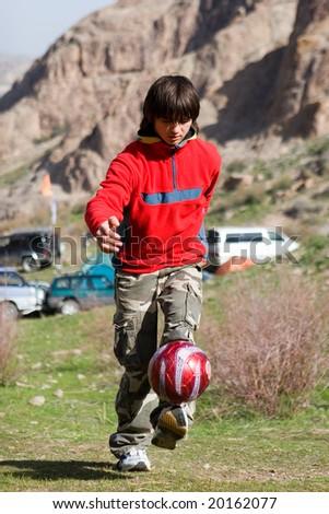 Teenager playing football - stock photo