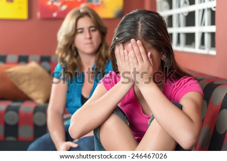 Teenager problems - Sad teenage girl cries with her worried mother on the background - stock photo