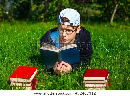 Teenager read a Books on the Grass