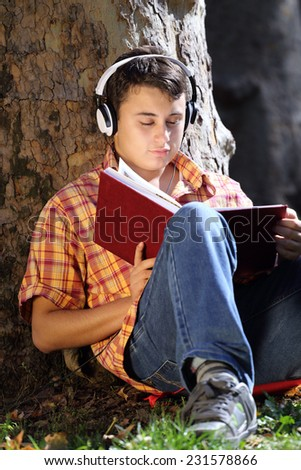 Teenager reading book outdoor in park - stock photo