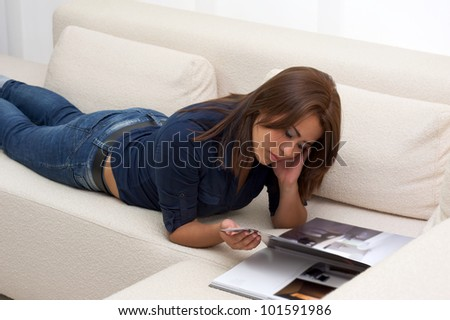 Teenager relaxing on the sofa, and reading a book - stock photo